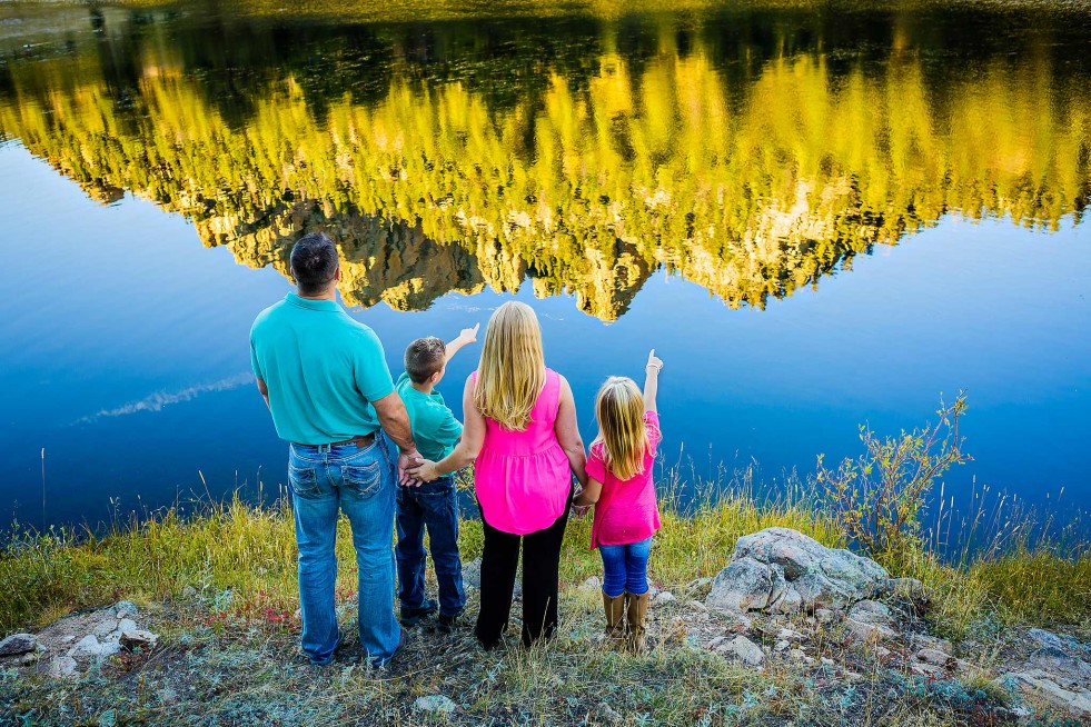 Family portrait near lake with reflection of mountain in Estes Park, CO