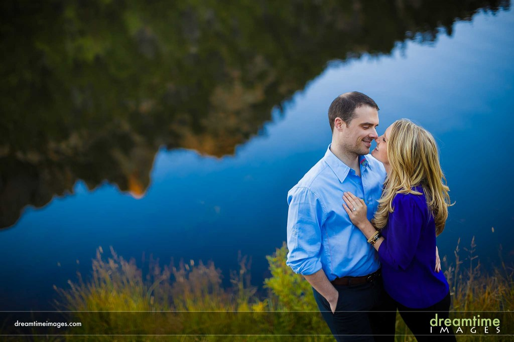 Engaged couple kissing by Lily Lake