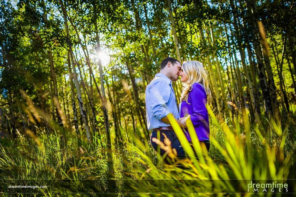 Couple kissing in aspen grove
