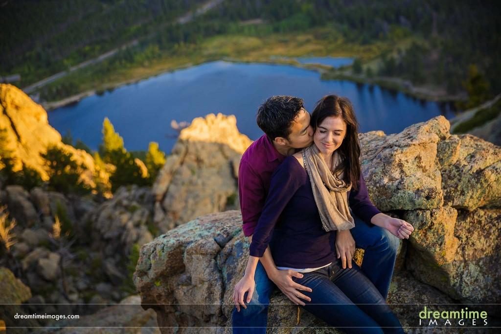 Engaged couple kissing above lake