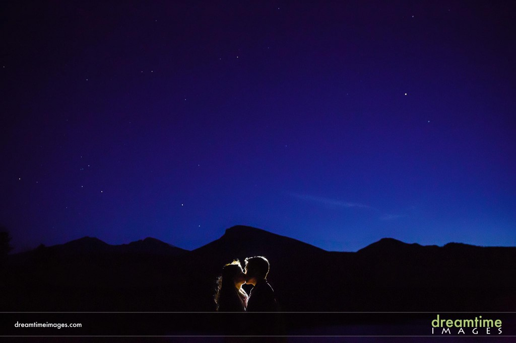 Engagement picture of couple kissing at night