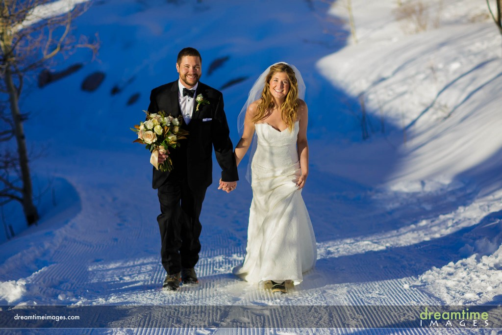 Bride and groom walking in snow in Beaver Creek