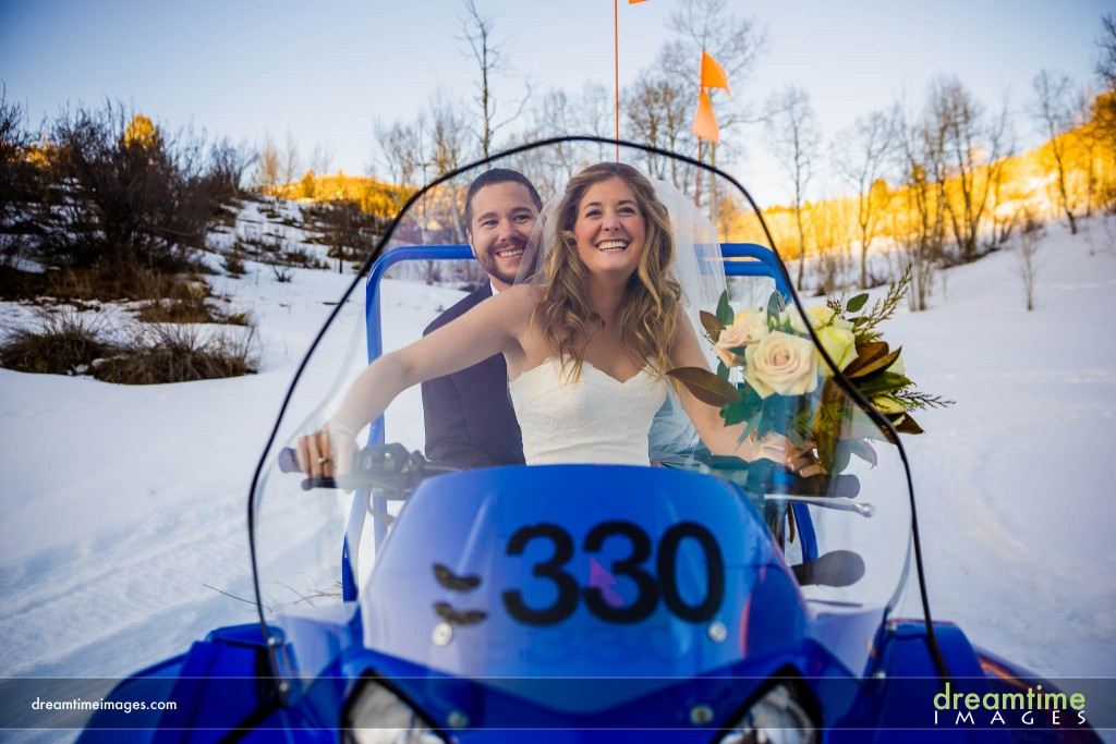 Bride and groom on snow mobile in Beaver Creek