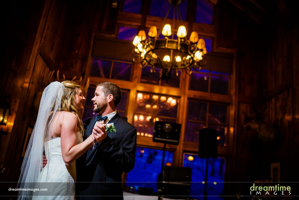 Bride and groom's first dance in front of picture windows in Saddleridge dining room in Beaver Creek