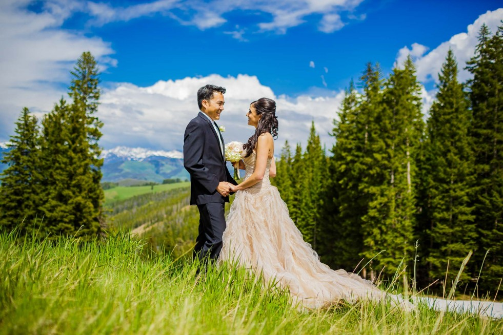 Wedding couple in field next to Beaver Creek Wedding Deck.