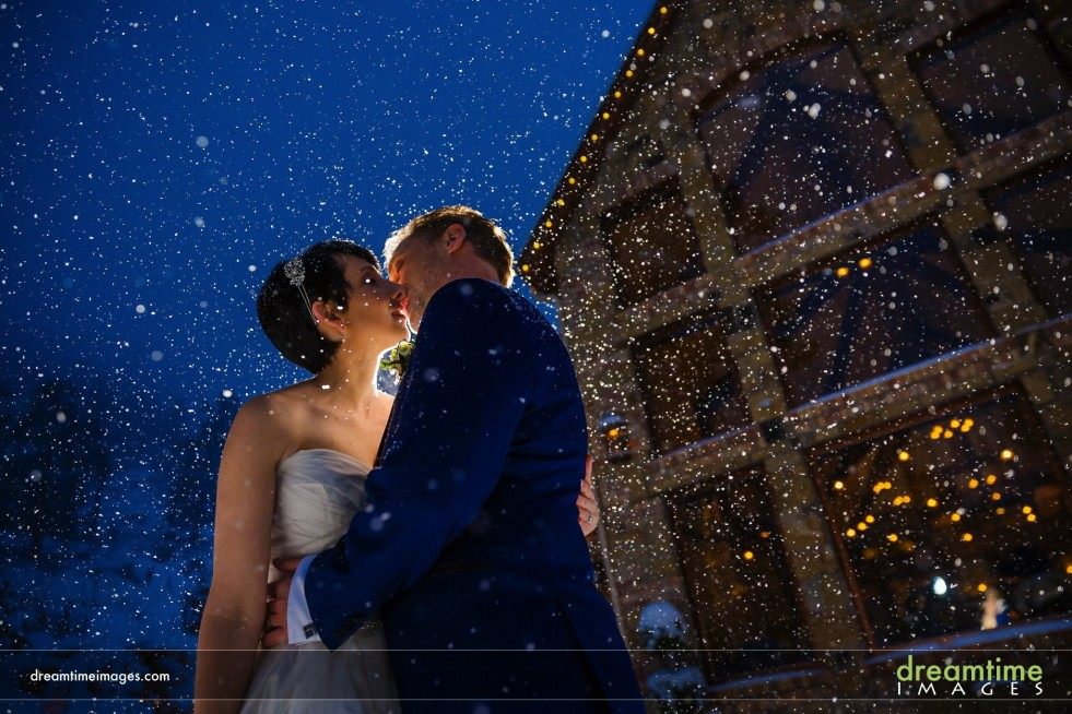 Bride and groom kissing in snow in front of Della Terra Mountain Chateau