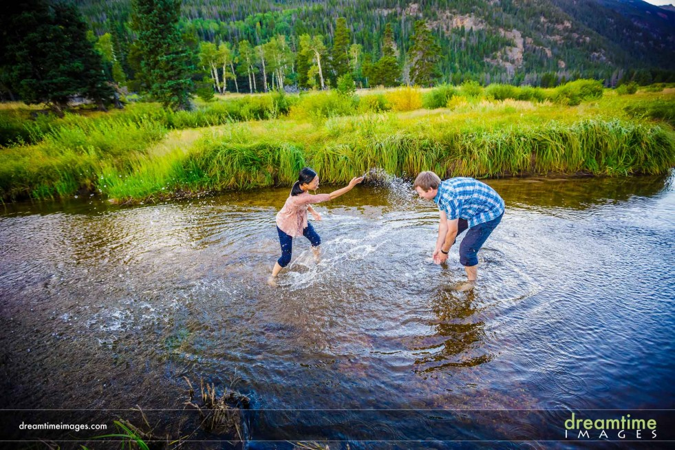 Engagement portrait of couple having water fight in river