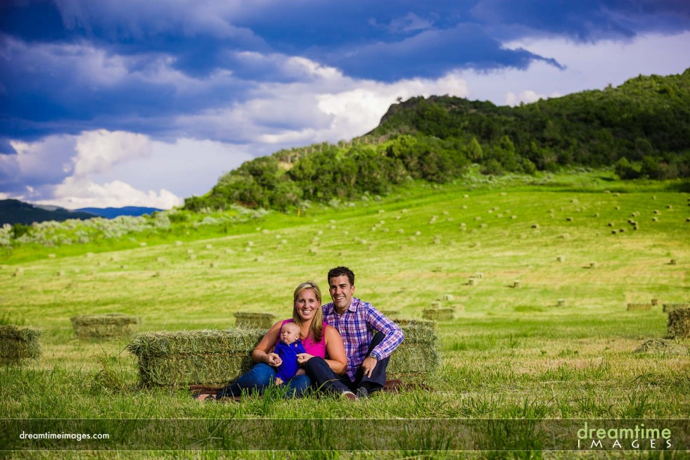 A couple and their child in a field at the turnoff to Snowmass