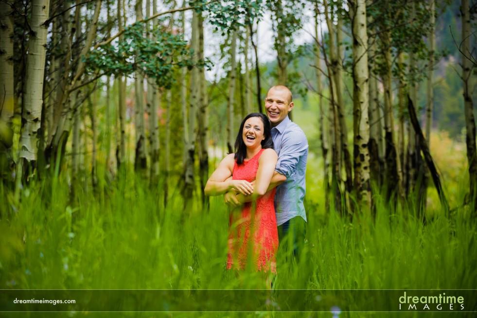A couple smiles in an aspen grove