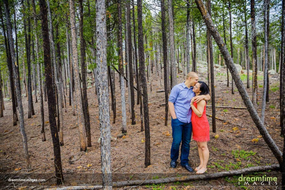 An engaged couple kiss in a forest in Colorado