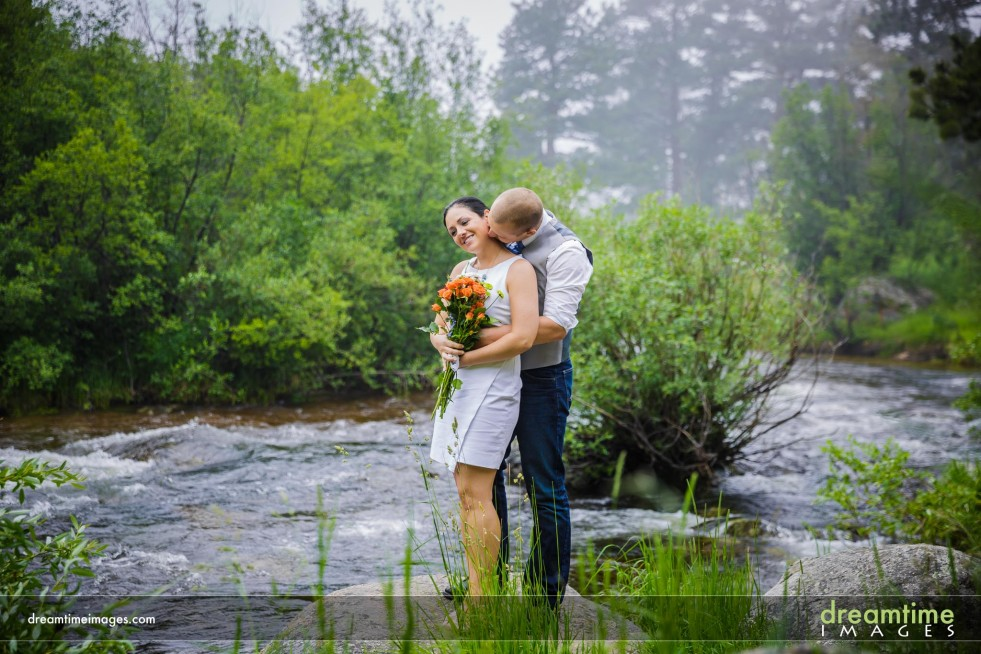 A bride and groom on a river bank at Wild Basin Lodge