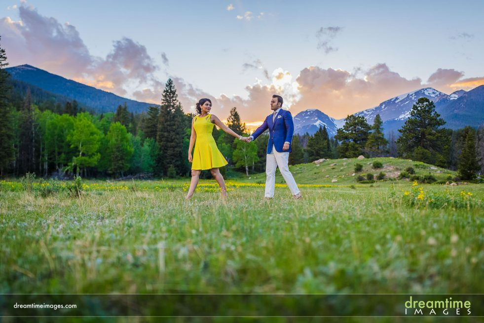 engaged couple walking through wildflowers in rmnp