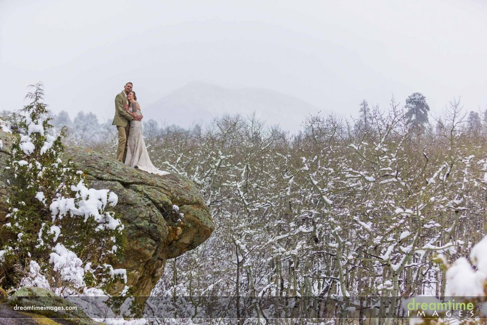 Wedding couple on rock outcrop in Estes Park